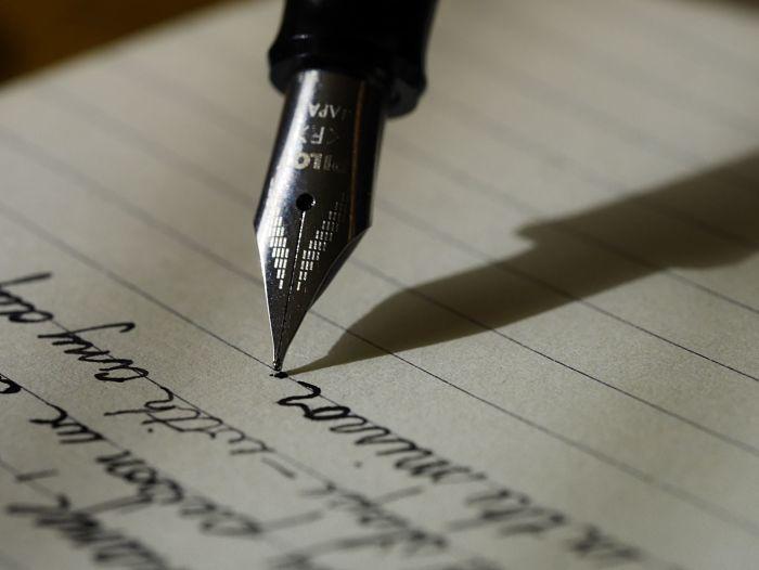 Кто-то пишет ручкой на листе