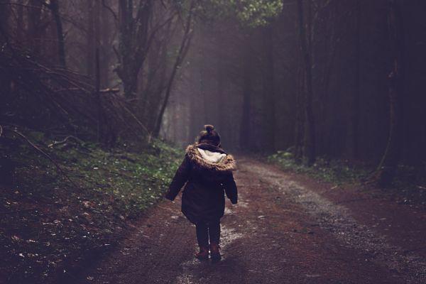 Маленькая девочка идет в лесу
