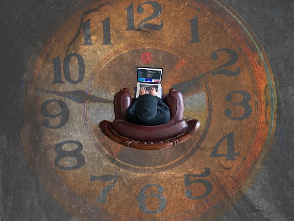 Человек работает за компьютером в середине циферблата